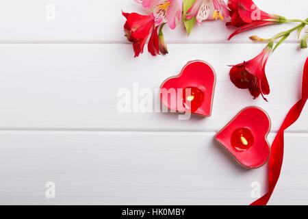Zwei herzförmige Kerzen, Band und roten Blüten auf dem weißen Tisch ...