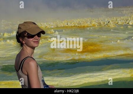 Frau in Hut und Sonnenbrille auf Dalol, Danakil-Senke, Äthiopien und lebendige gelb und grün die seltsame Kristallformen - Stockfoto