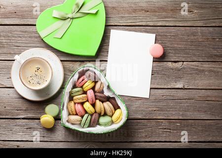 Bunte Macarons in Valentinstag herzförmigen Geschenk-Box und Kaffee Tasse auf Holztisch. Draufsicht mit Textfreiraum - Stockfoto
