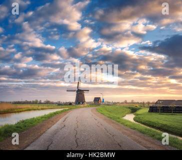 Straße mit Windmühle bei Sonnenaufgang in Niederlande. Schöne alte holländische Windmühle gegen bunte Himmel mit - Stockfoto