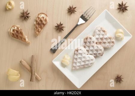 Herzförmige Waffeln mit Zitronenschale, garniert mit Powedered Zucker serviert auf einer Rectanangular Platte auf - Stockfoto