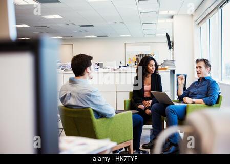 Eine Frau und zwei Männer sitzen in Sesseln in einem Büro miteinander zu reden. - Stockfoto