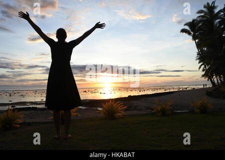 Silhouette einer touristischen Frau genießt dramatischen Sonnenuntergang an einem Strand in der Coral Coast, Viti - Stockfoto