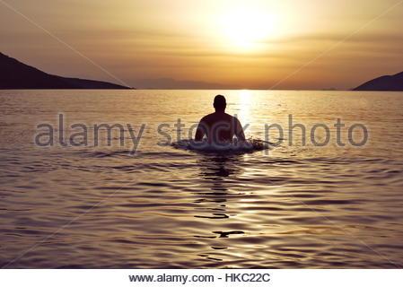 Spielerische Mann im Meer bei Sonnenuntergang - Stockfoto