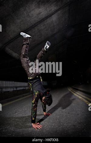 Ein Parkour-Freerunning-Sportler einen Handstand auf der Straße in der Nacht zu tun. - Stockfoto
