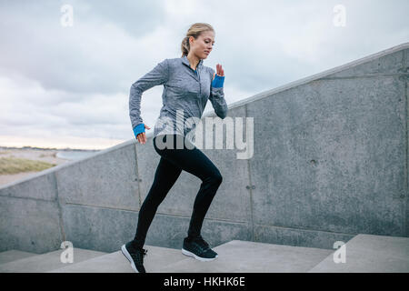 Aufnahme der jungen Frau, die im freien allein Treppe hinauf laufen. Fitness-Frau Ausübung auf Schritte. - Stockfoto