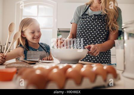 Frau knacken ein Ei in eine Schüssel mit Mädchen in der Küche stehen. Mutter und Tochter zusammen in der Küche zu - Stockfoto