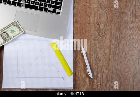 Krise-Diagramm unten Notebook mit Zeitplan Diagramm Dollar Geld Laptop auf Holztisch - Stockfoto