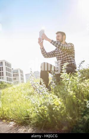 Junger Mann unter Selbstporträt Fotografie mit digitalen Tablet im Park, München, Bayern, Deutschland - Stockfoto