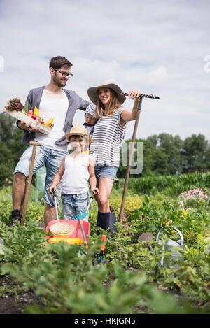 Familie Ernte Gemüse in gemeinschaftlichen Garten, Bayern, Deutschland - Stockfoto