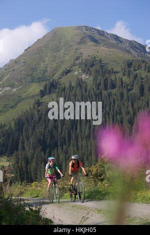 Zwei Mountainbiker fahren auf unbefestigten Straße durch Wald, Zillertal, Tirol, Österreich - Stockfoto