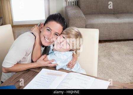 Portrait eines jungen umarmt seine Mutter während des Studiums, Bayern, Deutschland - Stockfoto