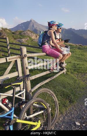 Junges Paar Mountainbiker mit Karte sitzen auf Holzzaun, Zillertal, Tirol, Österreich - Stockfoto