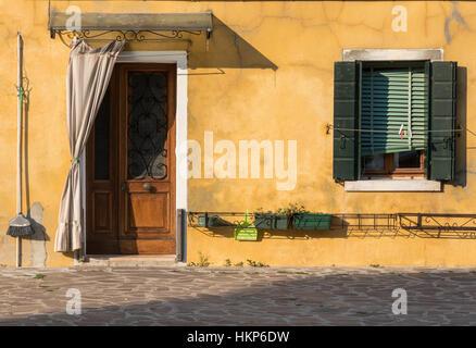 Foto einer bunten mediterranen Haus Fassade unter der warmen venezianischen Sonne in der Insel Burano. - Stockfoto