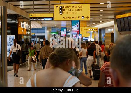 London, UK, 3. Juli 2009: viele Passagiere zu Fuß in Richtung A13-23 Tore in Heathrow Airport. Andere Richtung und - Stockfoto