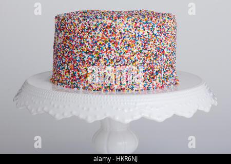 Kuchen auf eine Tortenplatte abgedeckt in weißen Zuckerguss und Regenbogen unerreichten Streusel mit einer Scheibe - Stockfoto