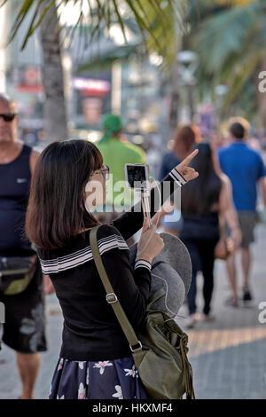 Japanische weibliche Touristen mit ihrem Smartphone zu verbinden und sprechen Sie mit ihrer Familie und Freunden - Stockfoto