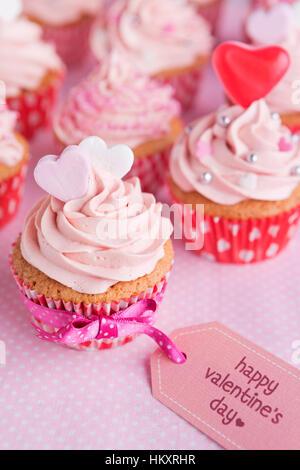 """Rosa Valentine Cupcakes mit den Worten """"Happy Valentine's Day"""" auf einem Schild. - Stockfoto"""