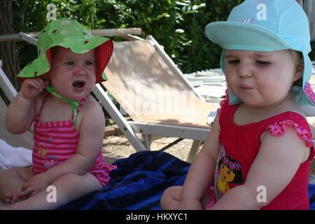 Lustiges Foto von Baby Mädchen, Badeanzüge und sun Hüte sitzen im Sommer Sonne unglücklich, lustige Kinder Konzept Kinder suchen Stockfoto