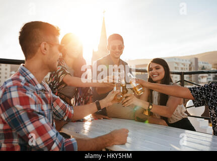 Glückliche junge Leute Toasten Getränke auf Party auf dem Dach. Junge Freunde hängen und mit Getränken genießen. - Stockfoto