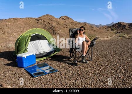 Frau in der Wüste aufrufenden Weile wird ihr Smartphone mit einem faltbaren Solarpanel geladen. - Stockfoto