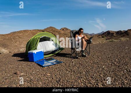 Frau in den Bergen mit ihrem Smartphone zu spielen, während des Ladevorgangs mit einem faltbaren Solarpanel. - Stockfoto