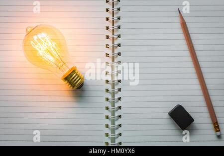 Notizbuch und Glühbirne - Stockfoto