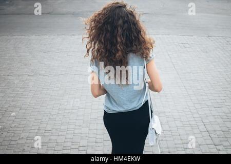 Schlanke junge Mädchen mit lockigen Haarpracht in einem Rock und Handtasche zu Fuß auf eine Stadt im Sommer, die - Stockfoto