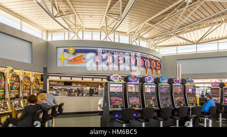"""Menschen spielen Spielautomaten am McCarran International Airport Terminal unter einem """"Welcome to Las Vegas"""" zu - Stockfoto"""