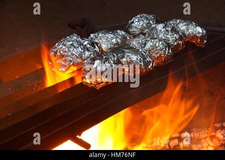 Eingewickelt in Alufolie auf ein Lagerfeuer kochen Kartoffeln. - Stockfoto