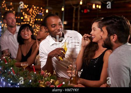 Freunde genießen eine Weihnachtsfeier zu sprechen, an der bar - Stockfoto