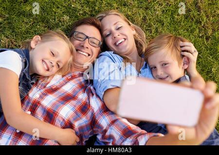 Junge weiße Familie liegen auf dem Rasen in einem Park unter einem selfie - Stockfoto