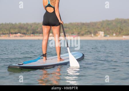 Halbe Backshot eines Mädchens auf einem stand-up-Paddle-Board in den Ozean vor einem Strand in der Nachmittagssonne. - Stockfoto