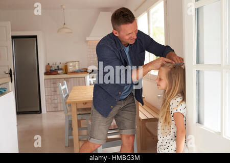 Vater Mess Tochter Höhe gegen die Wand - Stockfoto
