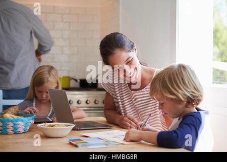 Kinder, die Hausaufgaben am Küchentisch mit Mama, Nahaufnahme - Stockfoto
