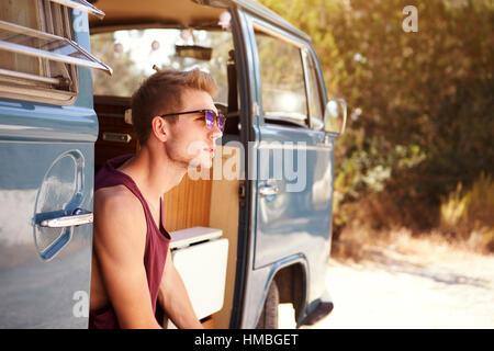 Junger Mann sitzt in der offenen Tür des Wohnmobil - Stockfoto