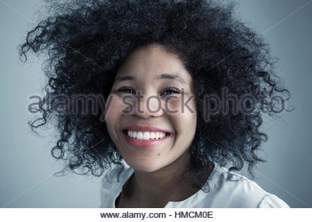 Nahaufnahme Portrait begeisterte Mischlinge junge Frau mit lockigen schwarzen Afro-Haar - Stockfoto