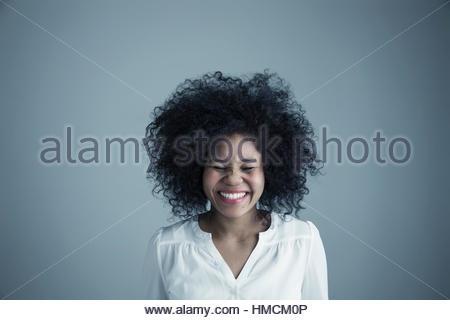 Porträt begeistert Mischlinge junge Frau mit lockigen schwarzen Afro-Haar mit geschlossenen Augen lachen - Stockfoto