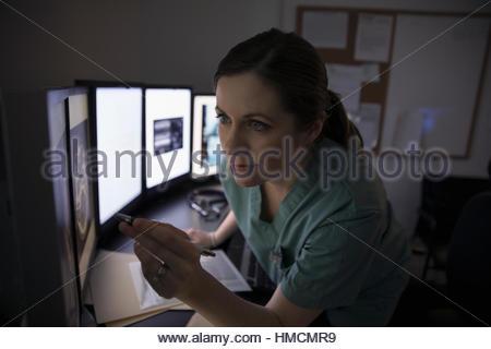 Fokussierte Krankenschwester digitales Röntgen auf Computern in dunklen Klinik Arzt überprüfen - Stockfoto