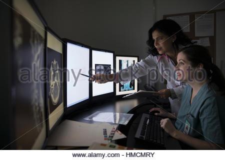 Ärztin und Krankenschwester, Prüfung und Diskussion über digitales Röntgen auf Computer in dunklen Klinik Arzt - Stockfoto