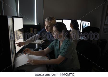 Weiblichen Krankenschwestern anzeigen und digitales Röntgen auf Computern in dunklen Klinik Arzt diskutieren - Stockfoto