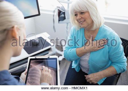 Ärztin, die über digitale Schulter Röntgen auf digital-Tablette mit älteren Patienten in Klinik Untersuchungsraum - Stockfoto