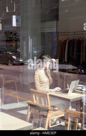 Junge schöne italienische Mädchen sitzen in einem Café Boutique einen Cappuccino und eine Zeitschrift liest und - Stockfoto