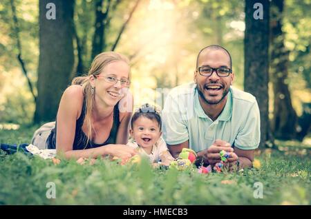 Interracial Familienglück ist einen Tag im Park genießen. Kleinen Mullato jungen. B&W schwarz / weiß Bild. - Stockfoto