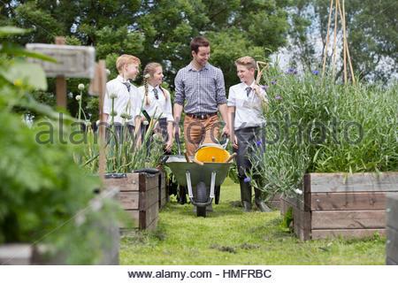 Lehrer und Schüler der Mittelstufe mit Schubkarre lernen Gartenarbeit im Gemüsegarten - Stockfoto