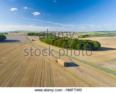 Luftaufnahme der Transport von Strohballen auf Anhänger nach der Ernte - Stockfoto