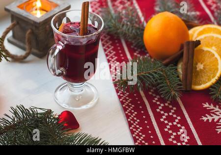 Glas heißer Glühwein auf Holztisch mit Kerze, Orange, Zimt und Weihnachtsbaum. Winter, Weihnachten, Neujahr Ferienkonzept - Stockfoto