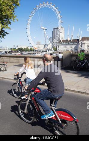 im mittleren Alter Mann und Frau Reiten Santander Fahrradverleih auf Ost-West-Zyklus Superhighway mit London Eye - Stockfoto