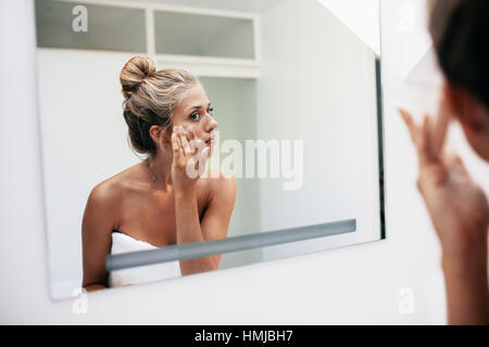 Reflexion einer Frau im Badezimmerspiegel kosmetische Creme im Gesicht auftragen. Frauen setzen auf Feuchtigkeitscreme - Stockfoto