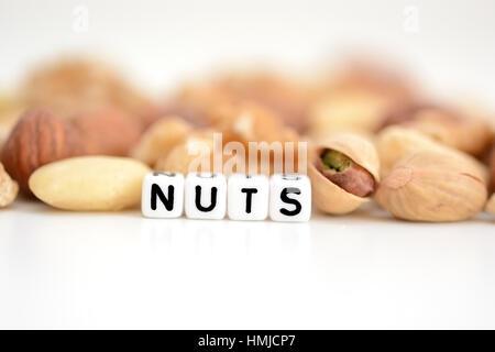 """Rohe Nüsse und das Wort """"Nuts"""" von Fliesen- buchstaben Perlen verteilt auf einem weißen Tisch geschrieben"""